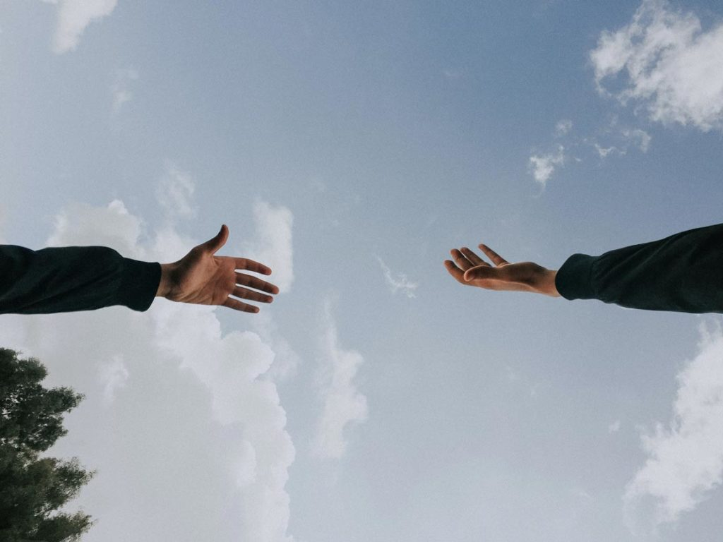 Deux mains de deux personnes différentes essayant de se toucher