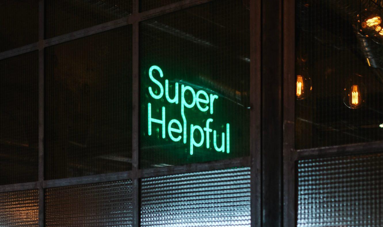 """Enseigne led dans la rue sur laquelle est écrit """"Super Helpful"""""""