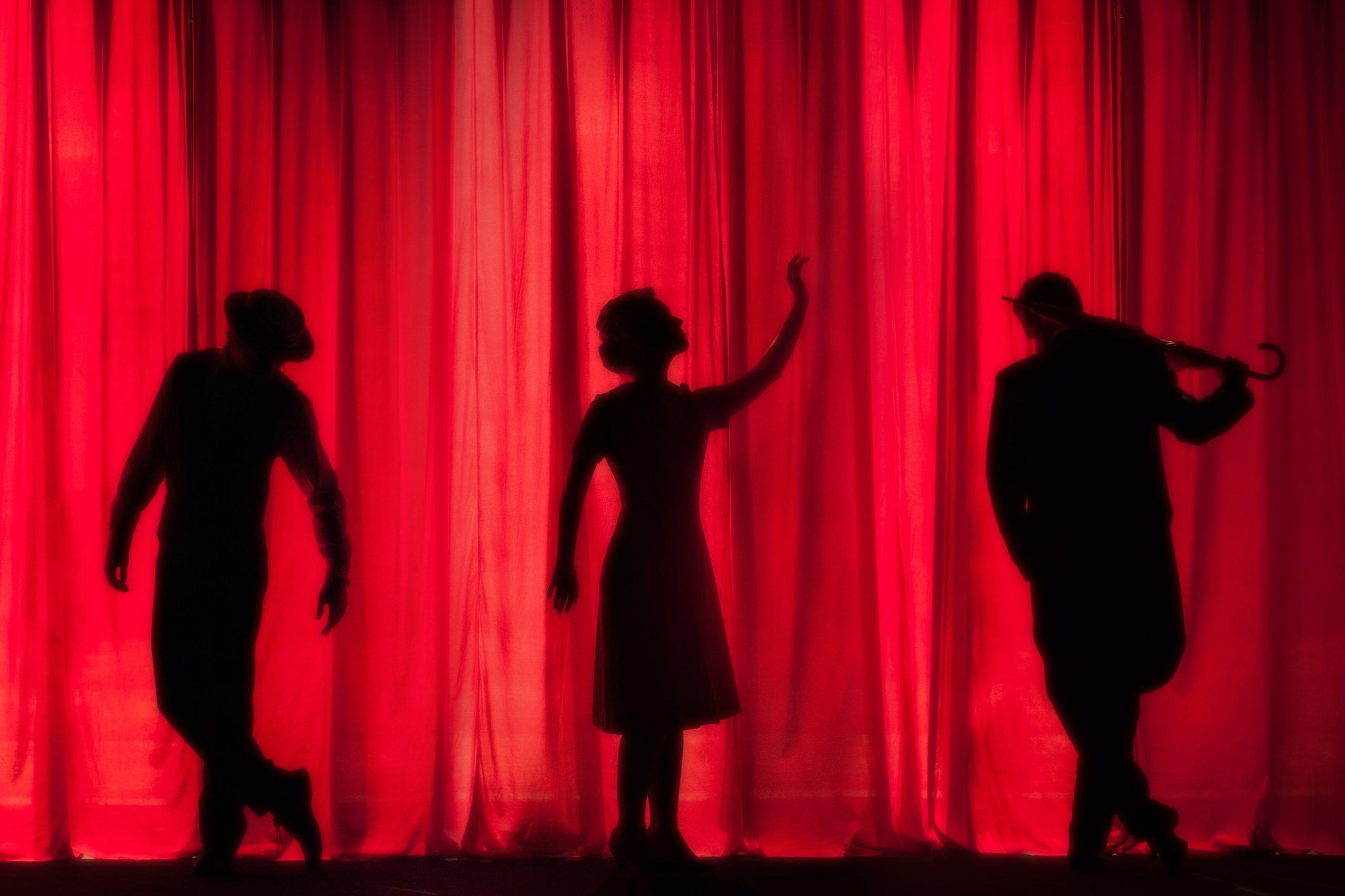 Photo des ombres de trois comédiens sur un rideau rouge de théatre. Copyright photo : kyleunderscorehead (https://unsplash.com/@kyleunderscorehead)