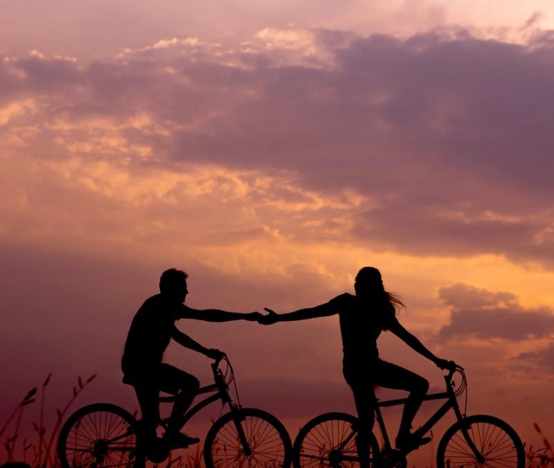 Deux cyclistes se donnant la main sur un soleil couchant