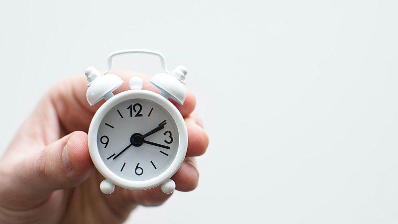 Photo d'une main qui tient un petit réveil